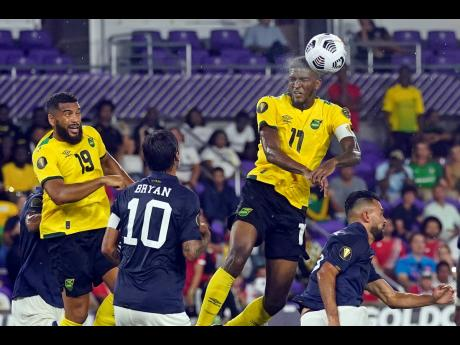 Jamaica's Damion Lowe (right) heads the ball towards goal in front of Costa Rica midfielder Bryan Ruiz (10) and defender Giancarlo Gonzalez (right) during last night's Concacaf Gold Cup Group C match in Orlando, Florida. At left is Jamaica's defender Adrian Mariappa.